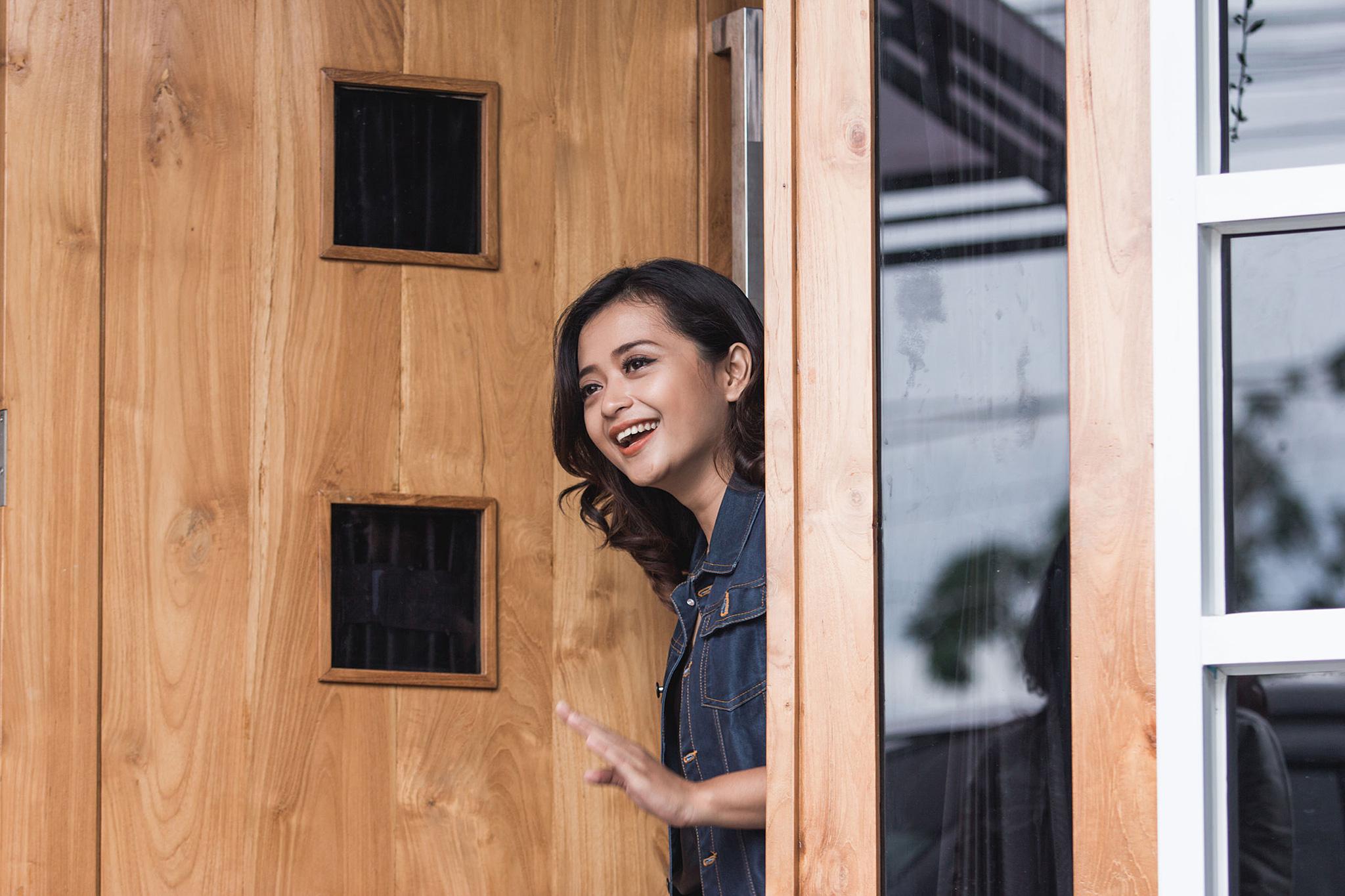Frau öffnet freundlich die Haustür